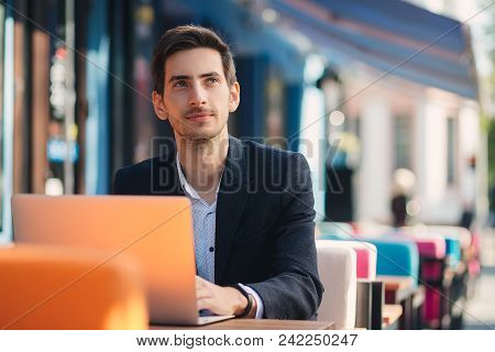 Young Modern Entrepreneur Working On Laptop Sitting At The Table In A Colorful Cafe. Ambitious Freel