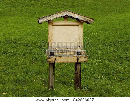 Old Wooden Sign Board On Green Grass. Rustic Wood Signboard In Shape Of Small House With Roof. Retro