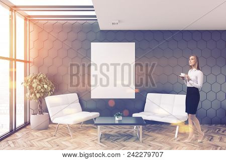 Blonde Busineswoman In A Gray Honeycomb Wall Pattern Office Lounge With Loft Windows, A Coffee Table