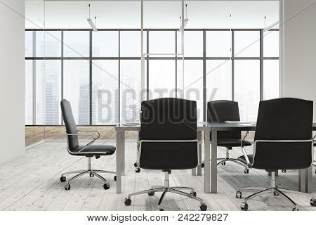 Loft Office Conference Room With A Wooden Floor, A Long Table With Black Chairs Near It And A Modern