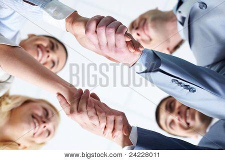Below view of four people handshaking