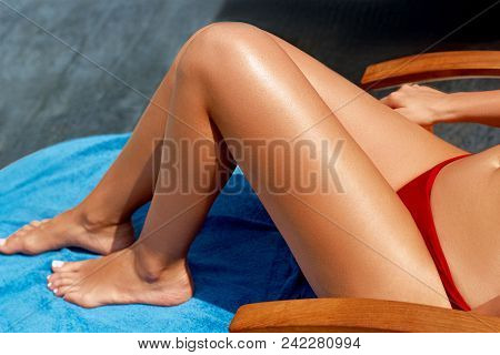 Woman Apply Sun Cream Protection Cream On Her Smooth Tanned Legs. Beautiful Legs Outdoors By On Whit