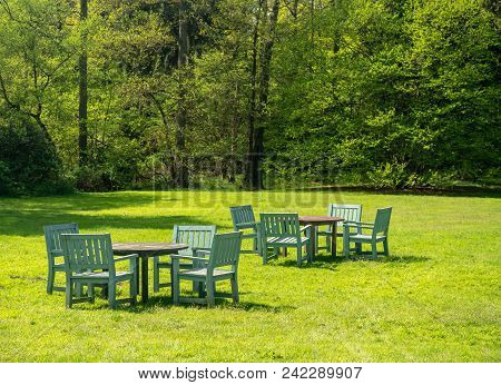 Teak Garden Tables And Chairs In A Large Expansive Garden With Trees In Background