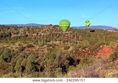 A Pair Of Hot Air Balloons Coming In For A Landing Near Sedona Arizona.