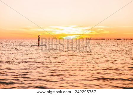 Woman Stand Up Paddle Boarding On A Quiet Sea With Beautiful Sunset