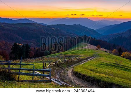 Country Road Winding Down The Hill At Dusk. Forested Mountain Ridge In The Distance. Lovely Scenery