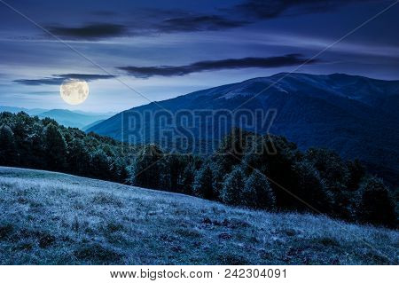 Beautiful Landscape Of Carpathian Mountains At Night In Full Moon Light. Forested Hills And Apetska