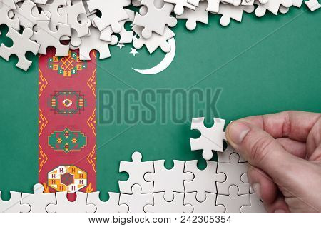 Turkmenistan Flag  Is Depicted On A Table On Which The Human Hand Folds A Puzzle Of White Color.