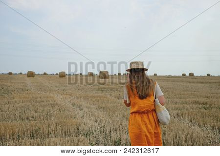 A Woman In A Straw Hat Walks Along A Wheat Field