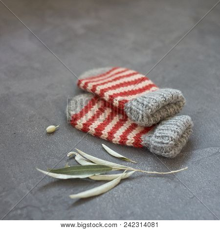 Mitten Gray With Strips Of Stripes With A Pattern On A Gray Background Closeup.