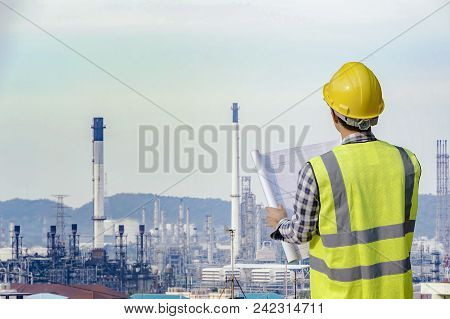 Engineer Explaining Oil Industry Discussing A New Project With Large Oil Refinery Background.