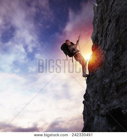 Explorer Man Climbs A High Danger Mountain With A Rope During Sunset