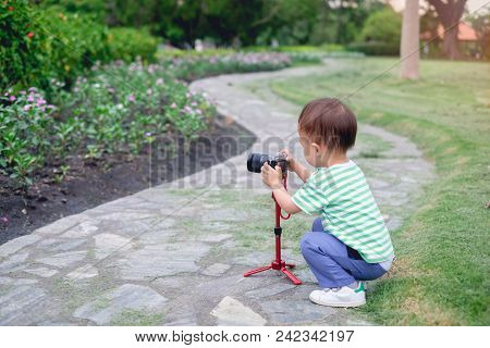 Cute Little Asian 2 Year Old Toddler Baby Boy Child  Taking Photo Using A Camera & Tripod, Looking A