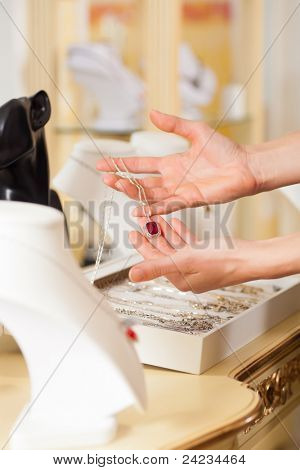 Female jeweller or designer presenting jewellery in her store