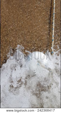 Sea Wave Crashing And White Buoy In The Sea Foam Surf. Nautical Rope With A Buoy. Wet Sand And The S