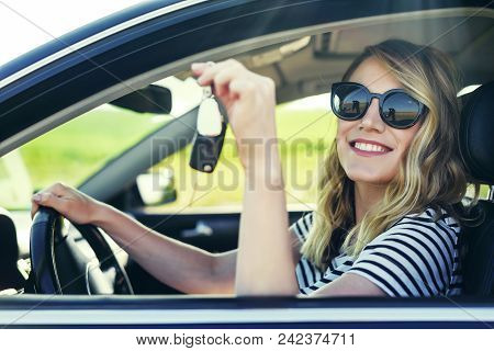 An Attractive Woman In A Car Holds A Car Key In Her Hand. Rent Or Purchase Of Auto - Concept.