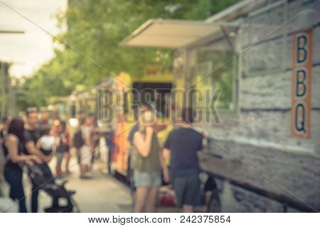 Vintage Blurred Food Truck Vendor With Customer Buy And Taste Variety Of Food
