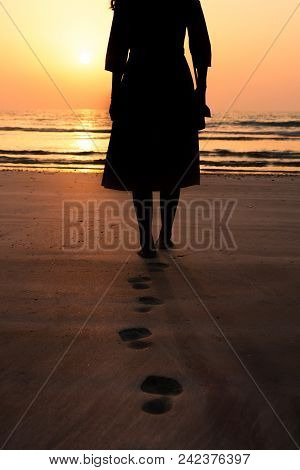 Silhouette Of A Woman Walking Towards Seaside At Sunset