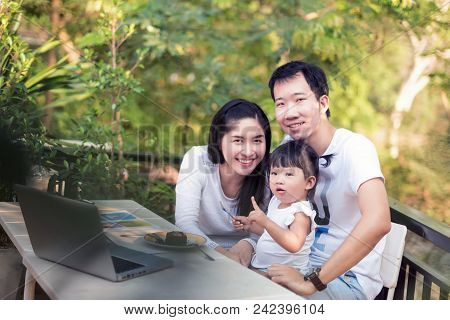 Happy Family Spending Time At Home And Eating Cake And Playing Computer; Family With Mother, Father,