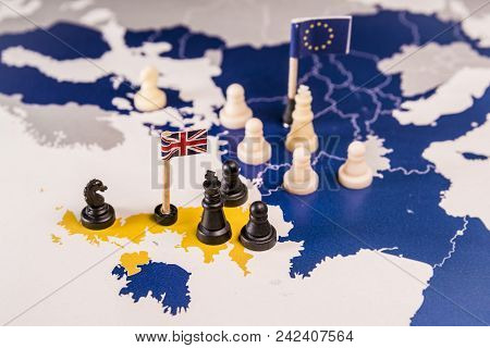 Chess Pieces And Flags On An European Map Focused In The Black Uk King And Islands. Brexit Negociati