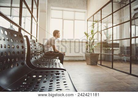 Side View Pensive Man Sitting On Modern Seats During Break At Job