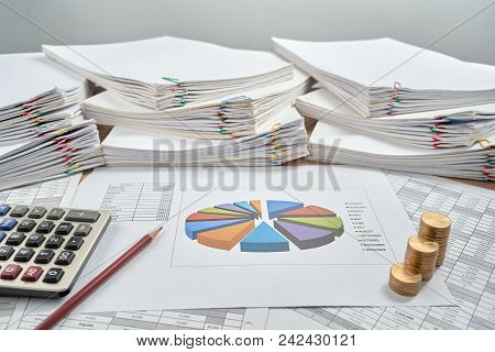Pencil And Pie Chart Of Sale Report Monthly With Step Pile Of Gold Coins And Calculator Have Blur Ov