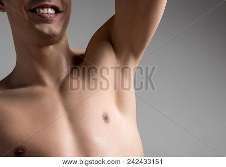 Close Up Of Armpit Of Cheerful Young Shirtless Man. He Is Standing With Raised Hand And Expressing S