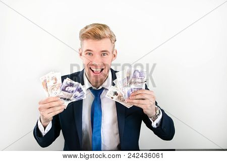 Man In Blue Suit Smiling And Grinning As He Holds Ten And Twenty Pound Notes In His Hands