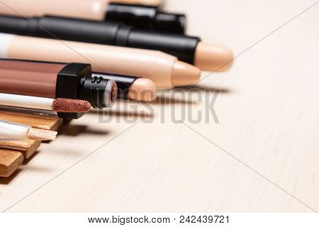 Make-up Products To Hide Skin Imperfections. Makeup Concealers And Foundation In A Row On White Wood