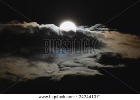 White Glowing Moon Disk In The Black Sky Is Blocked By A Strip Of Cumulus White Clouds With Brown Hi