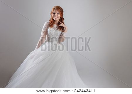 Lovely young woman bride in a lavish wedding dress. Charming young bride laughs, free space on the right poster