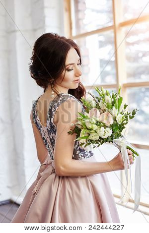 Woman In A Beautiful Dress And A Large Bouquet Of Flowers Near A Large Window. The Girl Is Waiting F