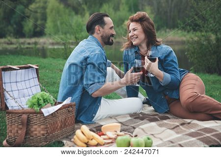 Joyful Middle-aged Married Couple Is Celebrating Their Anniversary In The Nature. They Are Drinking