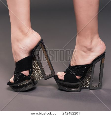 Fashionable Woman Slender Legs In Black Stylish High Heels Shoes With Rhinestones On Background