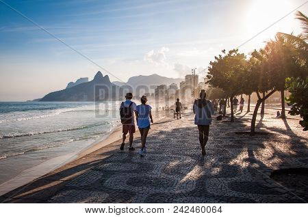 Rio De Janeiro, Brazil - May 24, 2018: People Walk On The Famous Sidewalk Of Ipanema Beach By Sunset