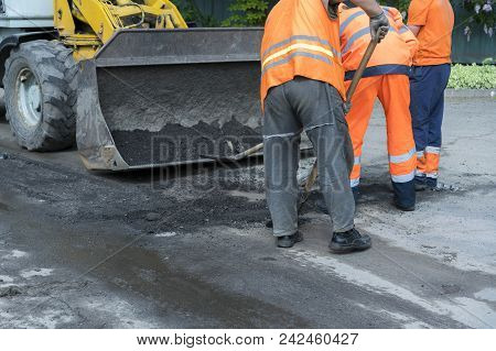 Workers On A Road Construction, Industry And Teamwork. Builders Workers At Asphalting Paver Machine