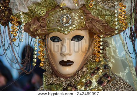 A Costumed Reveler Of The Carnival Of Venice In A Green And Yellow Costume Looking To The Right.