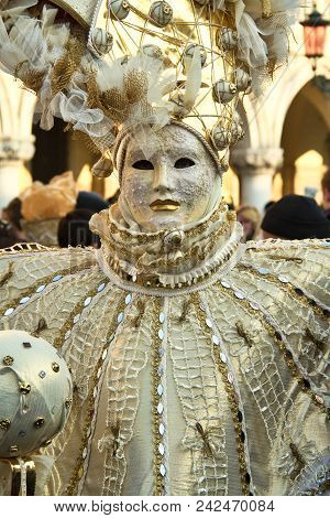 A Costumed Reveler Of The Carnival Of Venice In A White And Gold Costume Looking Directly At The Cam