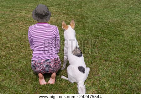 Female Master Shows To Young Dog How To Perform Sit Command