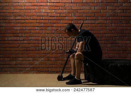 athlete is engaged in fitness for endurance in the hall against the background of the red wall poster