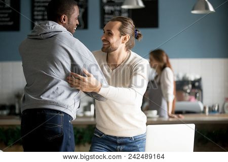 Smiling Diverse Male Buddies Embracing Greeting In Cafe, Happy Millennial Men Best Friends Reaching