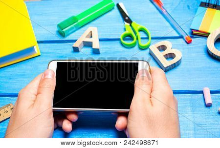 The Student Is Holding A Mobile Phone In The Background Of A Creative Mess On The Desktop. The Workp