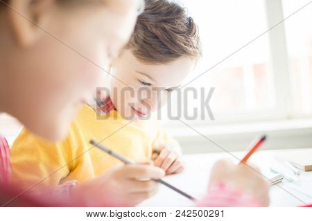 Cute youngster looking at picture on page of copybook of his classmate and discussing it