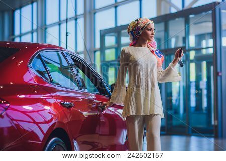 Property And People Concept - Muslim Woman In Hijab With Car Key Over Car Show Background. Happy Wom
