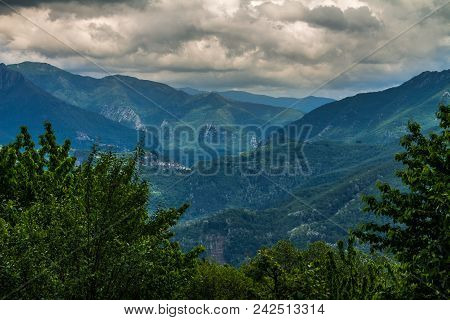Mountainous Landscape With Haze In The Distance And Cottony Clouds