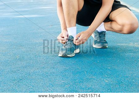 Young Male Runner Tying Shoelaces Old In Runner Exercise For Health Lose Weight Concept On Track Rub