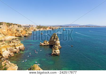 Scenic Cliffs And Grottos Explore By Tourists By Kayaks And Boats In Algarve, Portugal. Scenic Coast