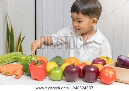 Healthy And Nutrition Concept. Kid Learning About Nutrition How To Choose Eating Fresh Fruits And Ve