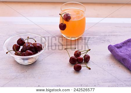 Fresh Delicious Red Cherry And Fresh Squeezed Orange Juice On Light Wooden Background. Fresh Ripe Ch