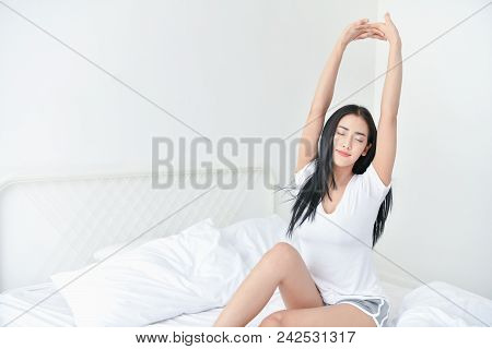 Lifestyle Concept. Cute Asian Girl In Night Dress. Beautiful Asian Woman Is Relaxing In A White Bedr